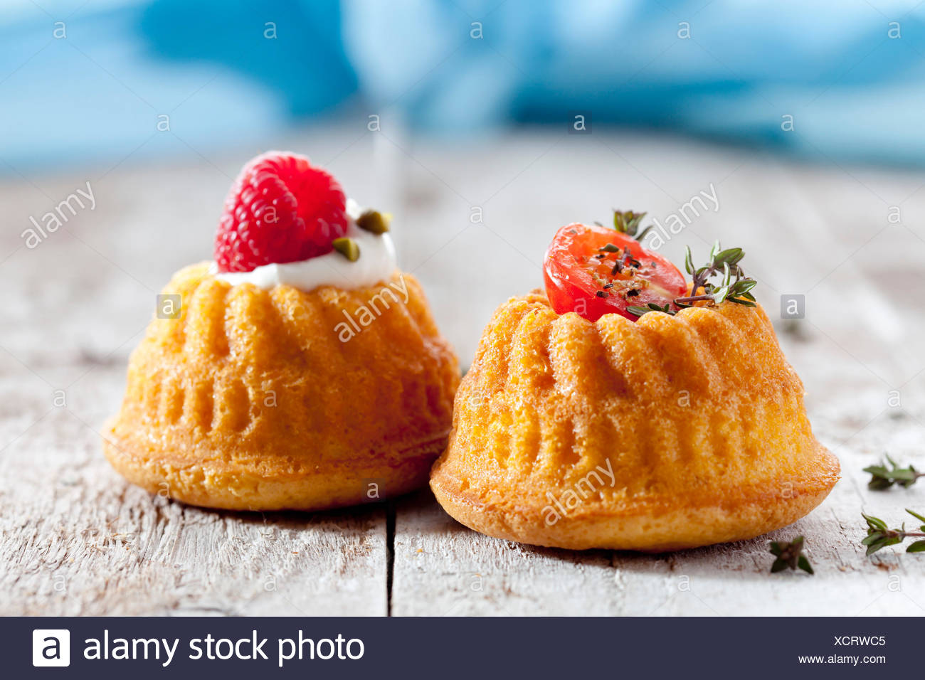 Two mini Gugelhupf filled with cream cheese and ricotta garnished with tomato and raspberry Stock Photo