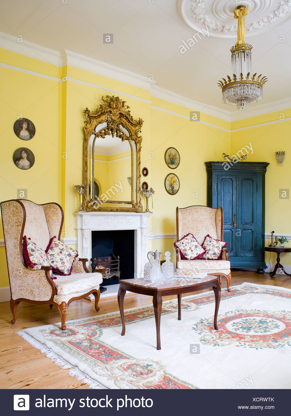 Ornate Gilt Antique Mirror Above Fireplace In Yellow Drawing Room With  Cream Wing Chairs On