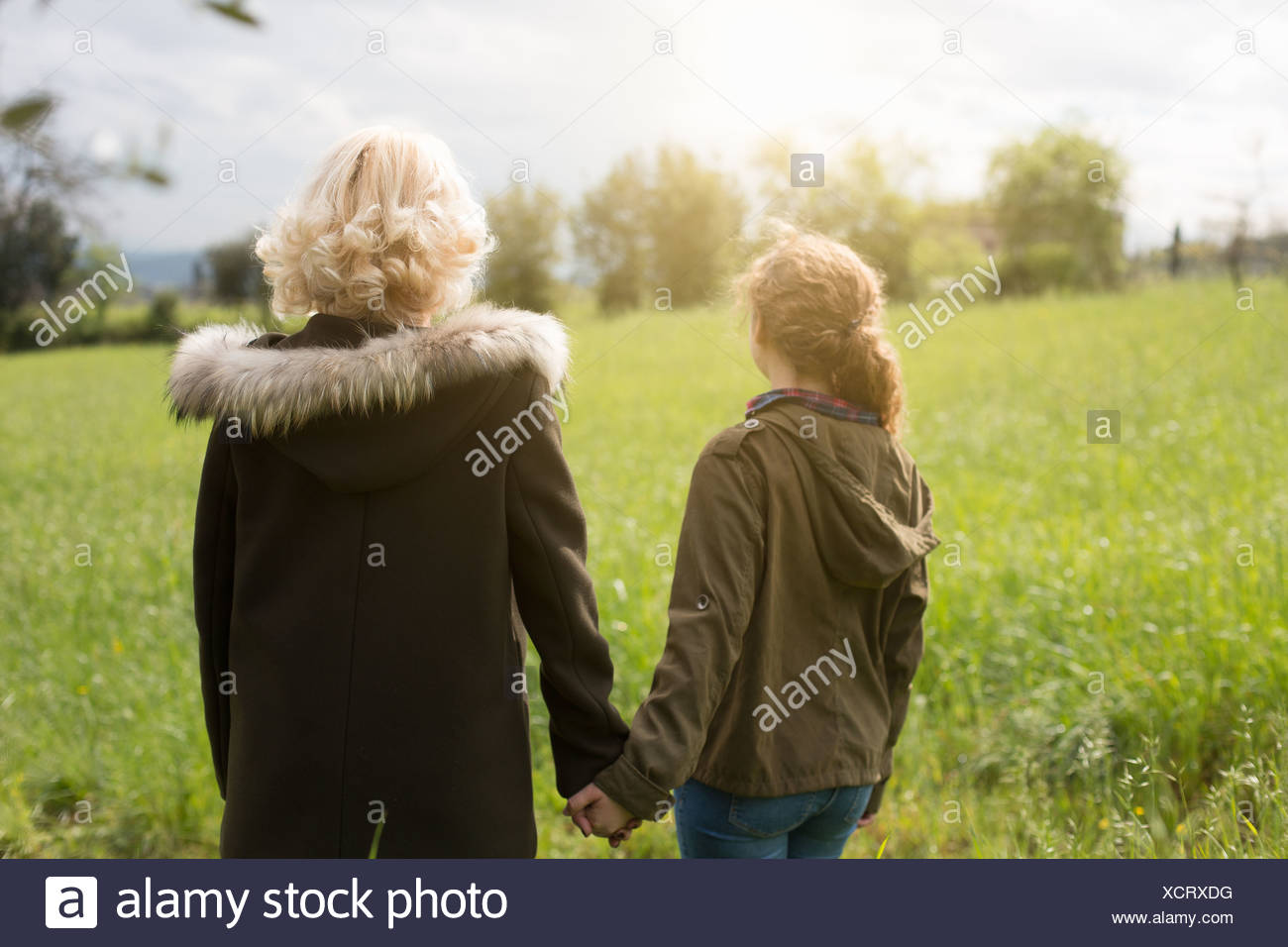Rear view of mother and teenage daughter holding hands - Stock Image