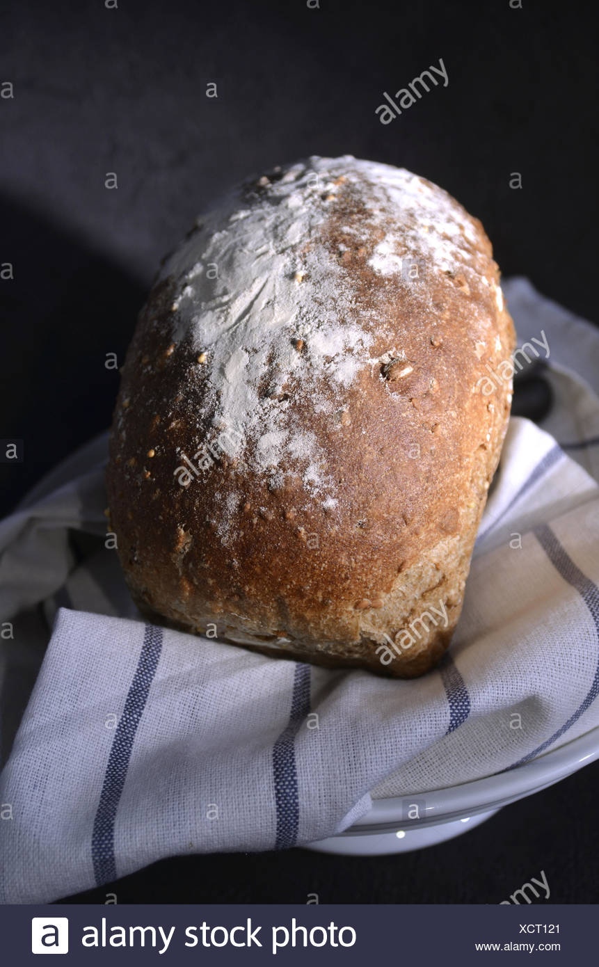 Flour dusted multi grain loaf of bread - Stock Image