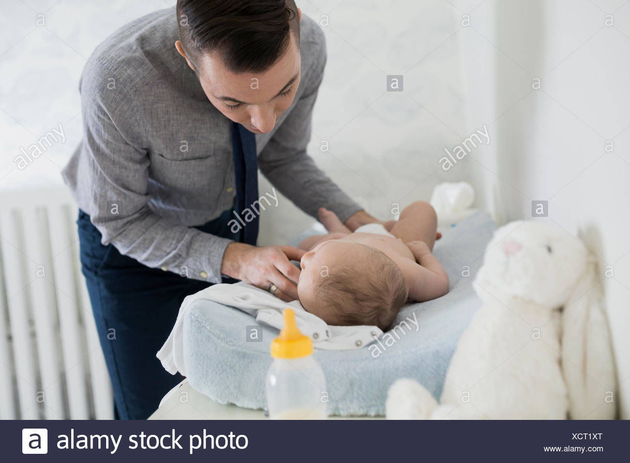 father changing baby diaper nursery 2-5 months - Stock Image