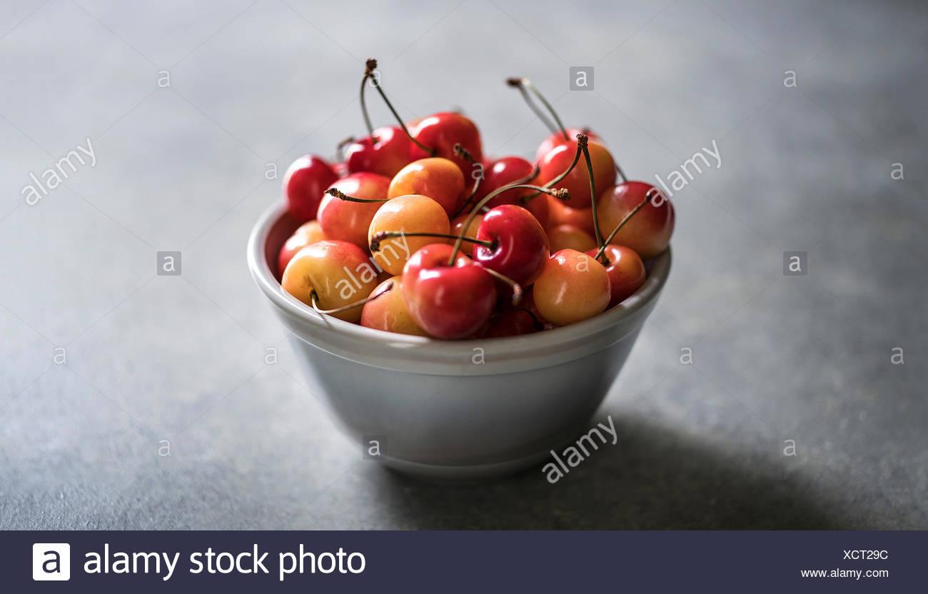 Ripe rainier cherries in gray bowl on gray concrete surface - Stock Image