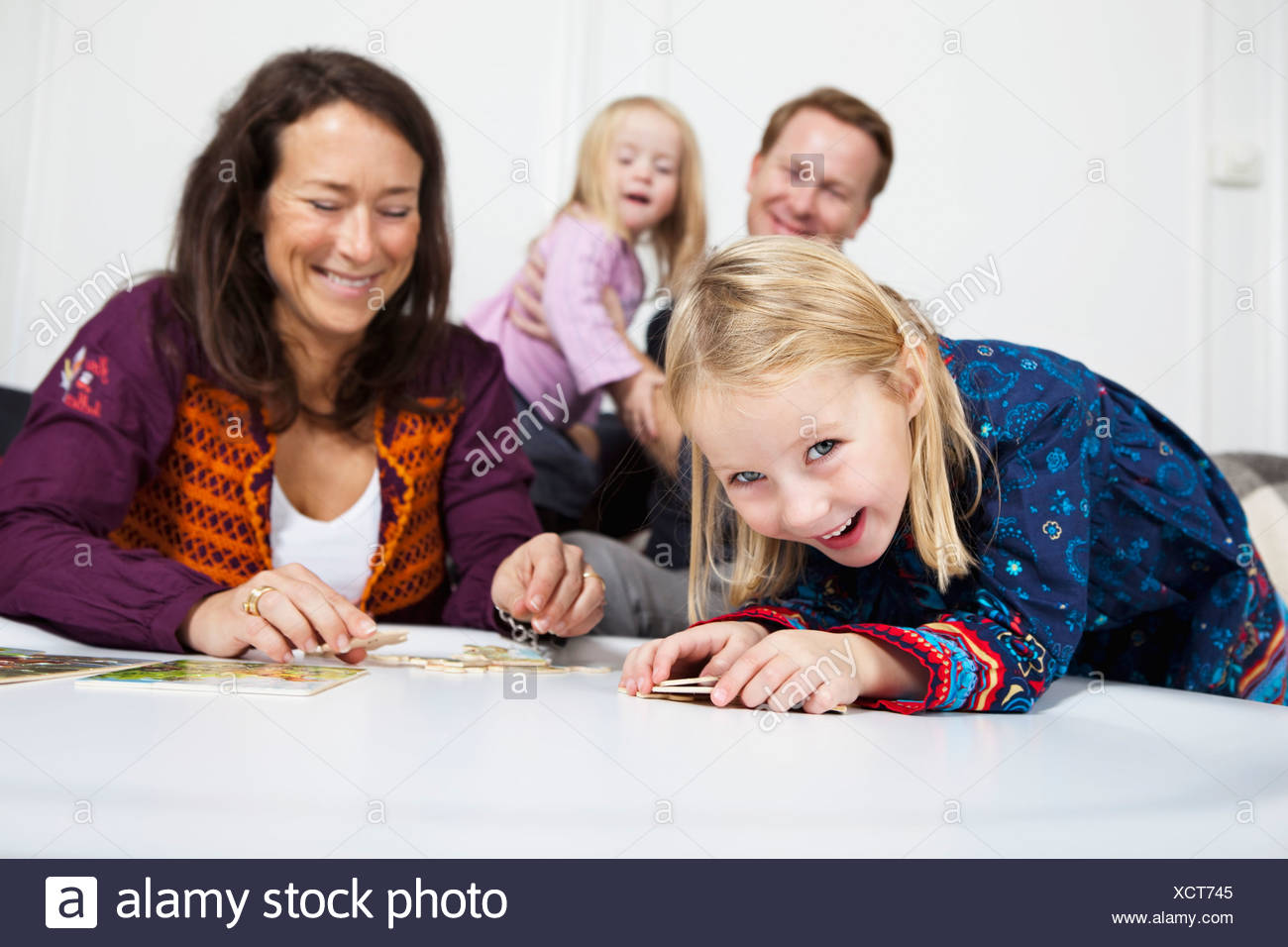 Parents and daughter (2-4) smiling - Stock Image