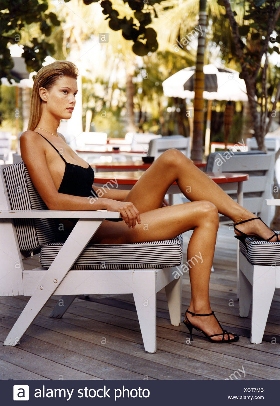 Female dark blonde straight hair worn tucked behind her ears wearing a plain black swimsuit thin straps and strappy black high - Stock Image