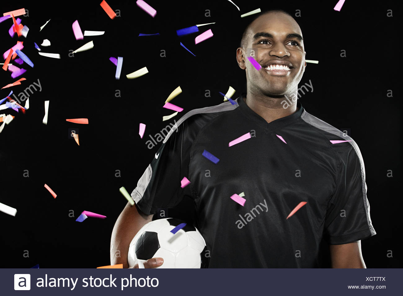 Footballer with falling confetti - Stock Image