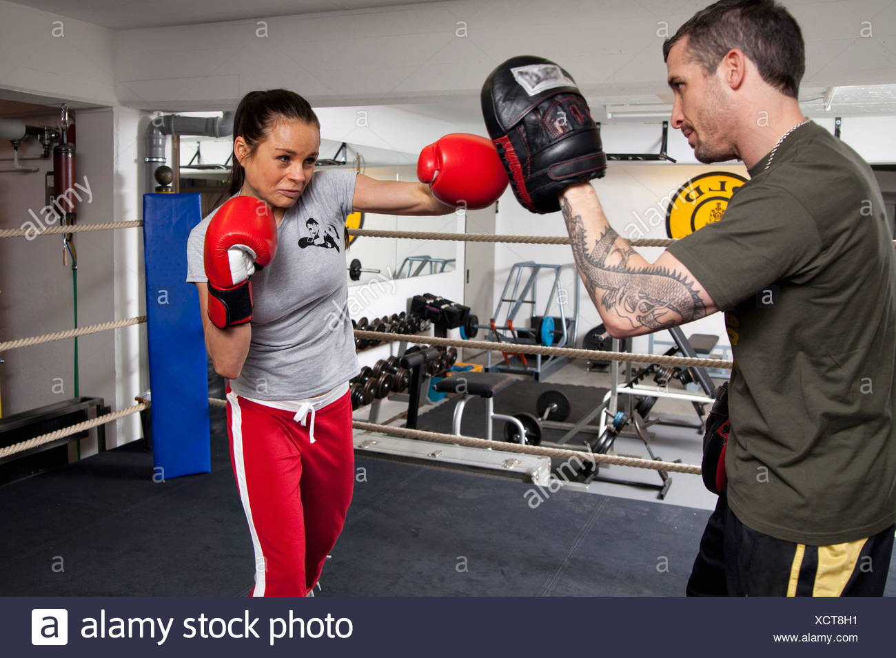 Young woman with coach in boxing ring - Stock Image