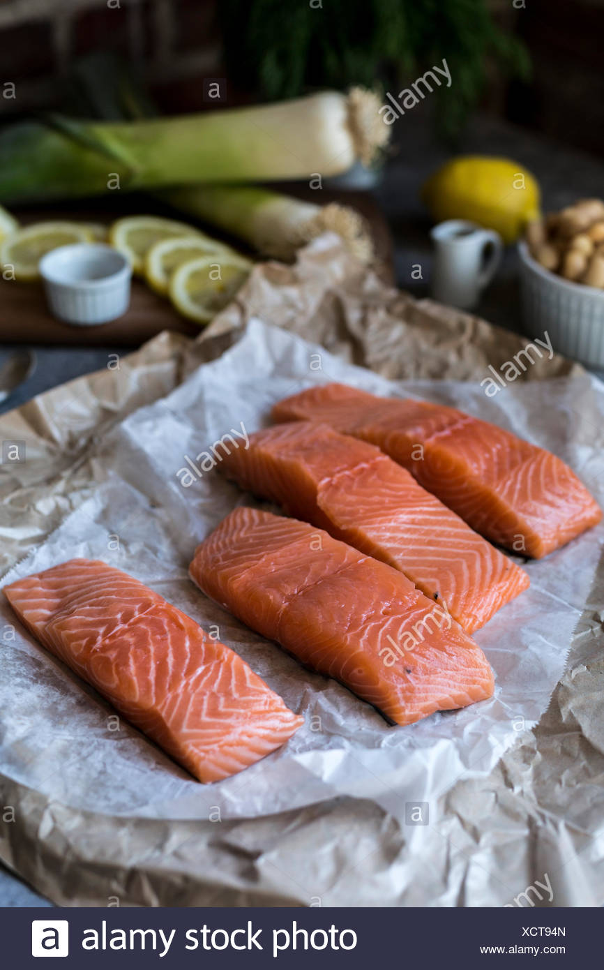 Four slices of fresh salmon, leeks, slices of lemon are photographed from the front view. - Stock Image