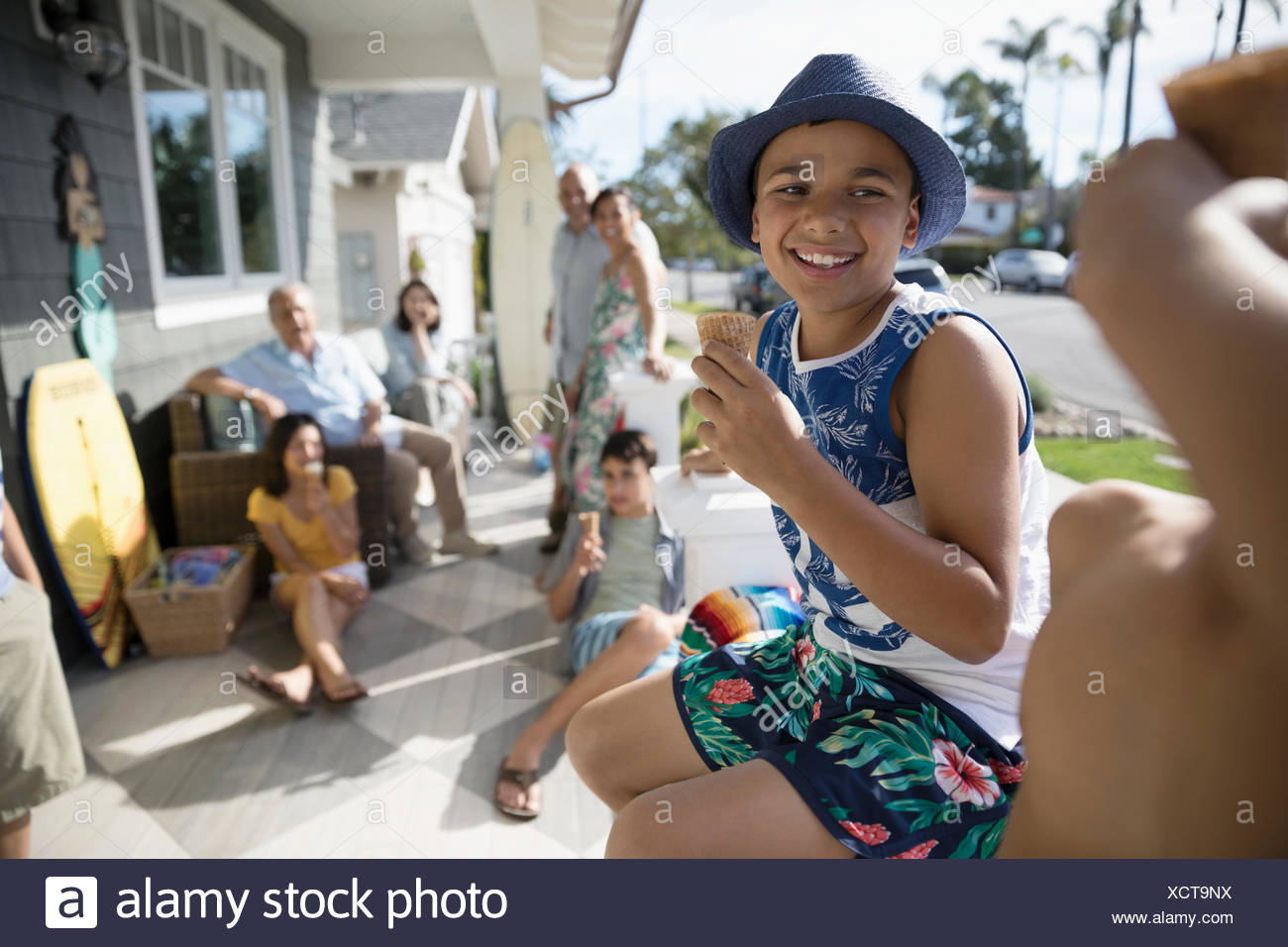Smiling boy eating ice cream cone with family on summer beach house porch - Stock Image