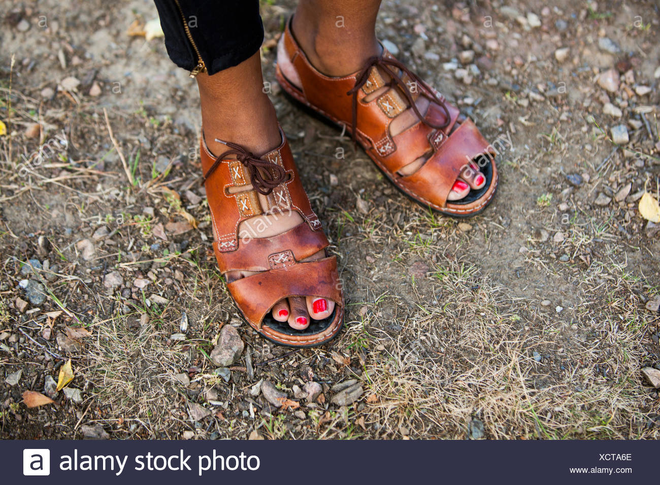 Low section of woman standing on dirt land - Stock Image
