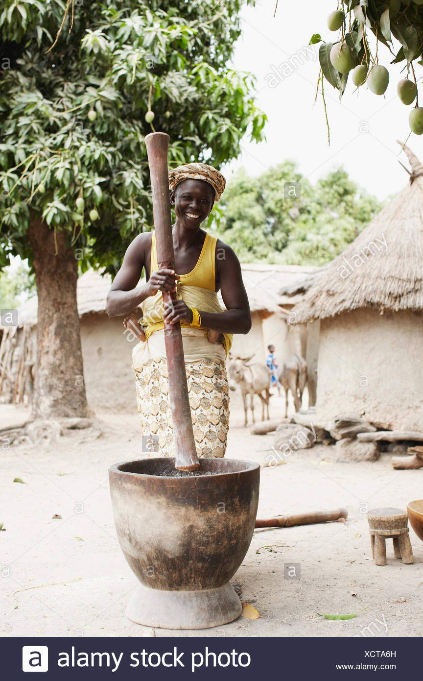 Woman Carrying Child On Back Grinding Corn To Flour Magadala Mali