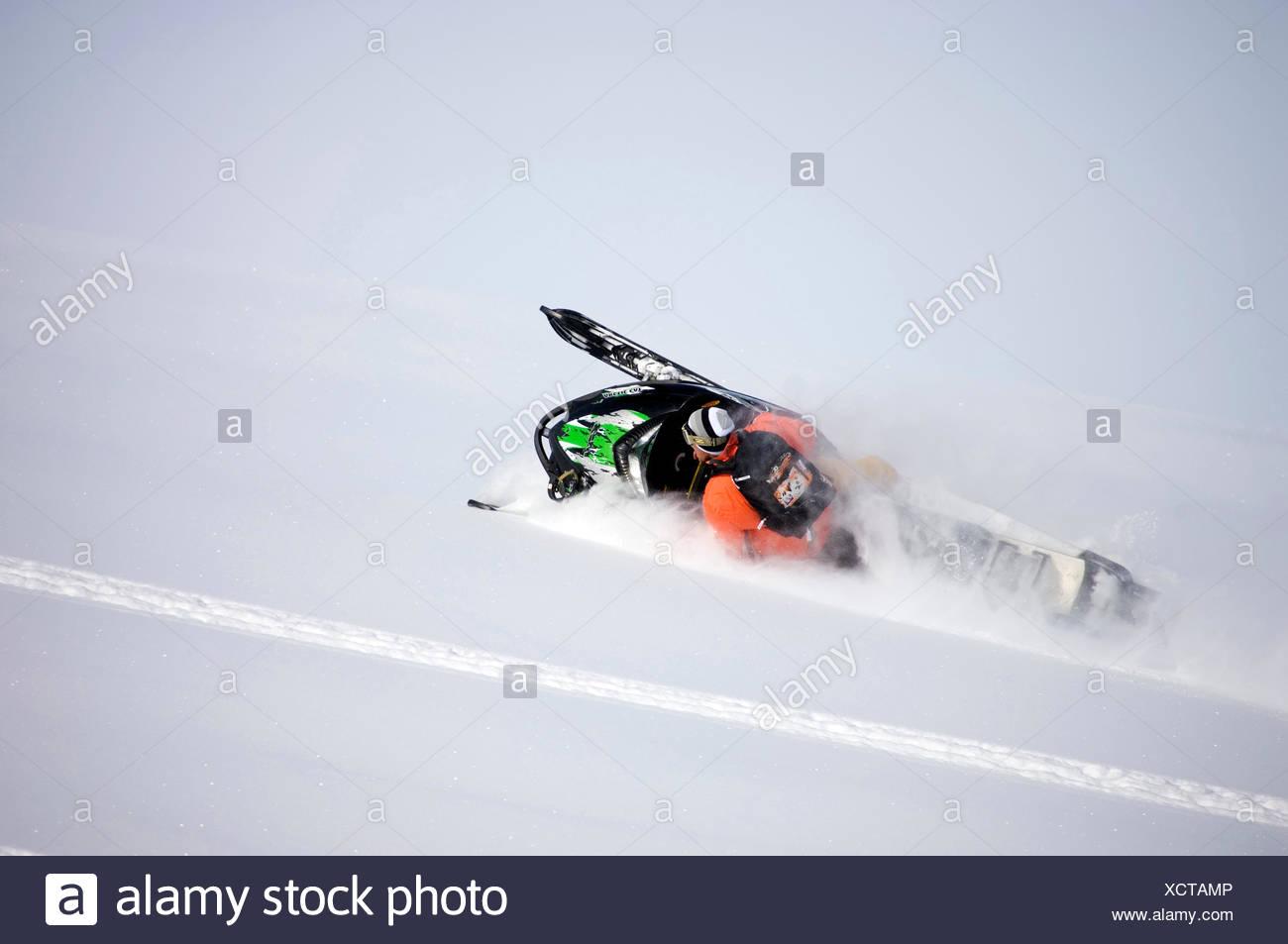 Scotty Lago side-hilling his snowmobile in Valdez, Alaska. - Stock Image