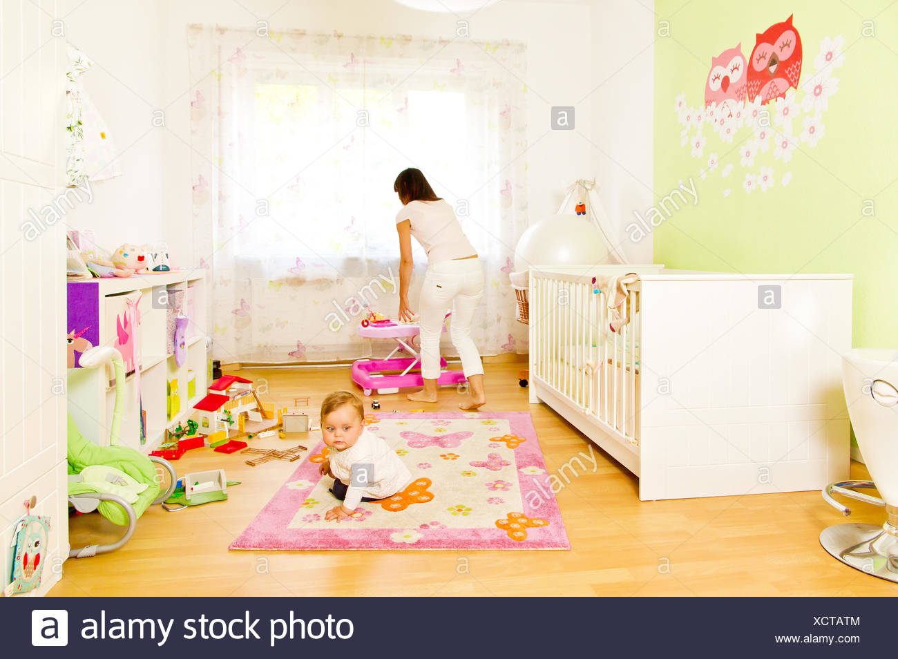 Young mother with baby in childrens room Stock Photo