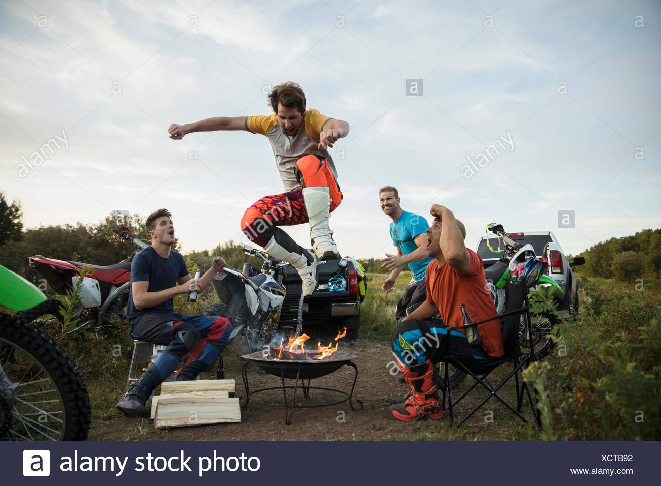 Friends watching man jumping over campfire near motorbikes - Stock Image