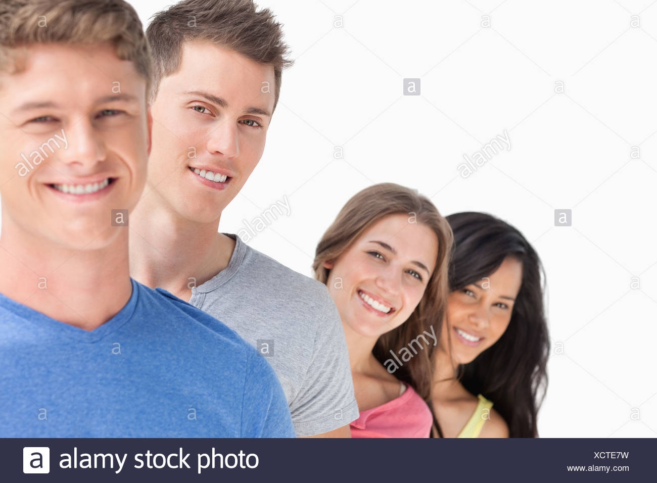 Four people standing one in front of the other with the girls heads angled out more - Stock Image