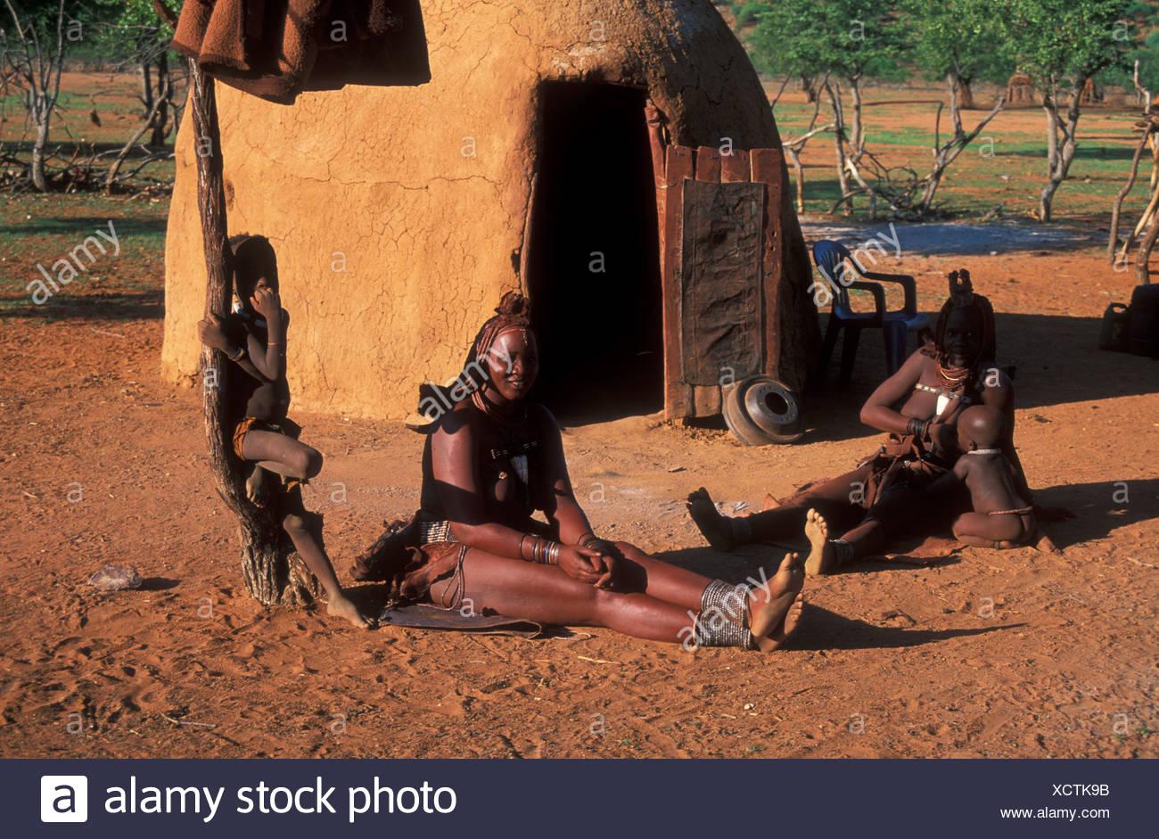 Africa children front headdress Himba hut inside Kaokoveld Kraal married Namibia Africa Ovahimbe tribe - Stock Image