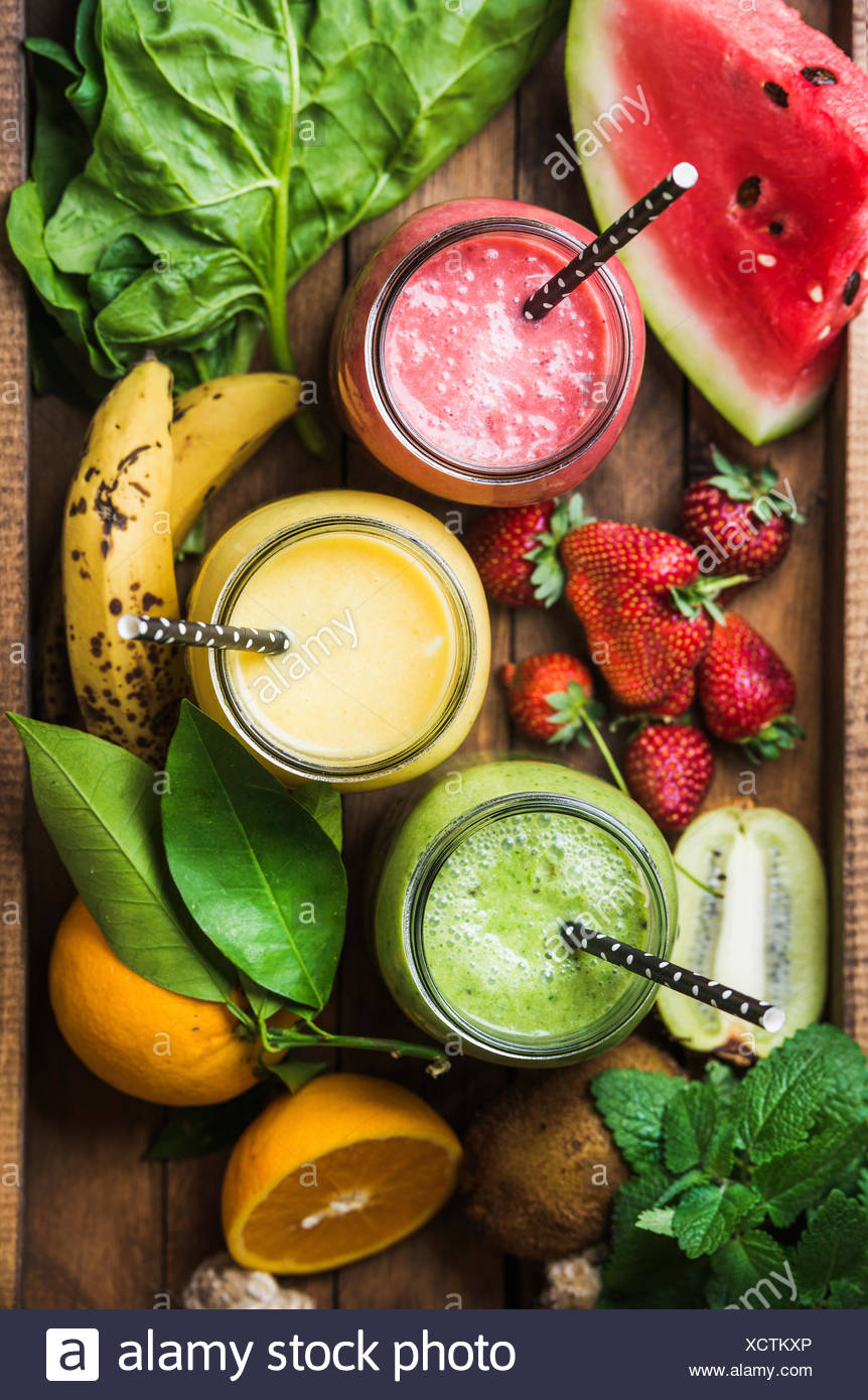 Fresh blended smoothies in glass jars with straws on wooden baclground served with watermelon, kiwi, orange, banana, strawberry, - Stock Image