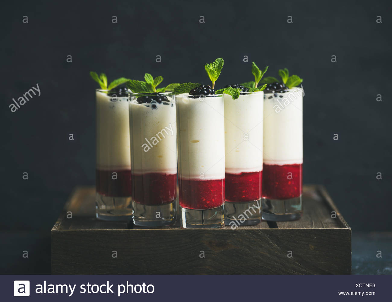 Catering, banquet or party food concept. Dessert in glass with blackberries and mint leaves over dark background on corporate event, christmas, birthd - Stock Image