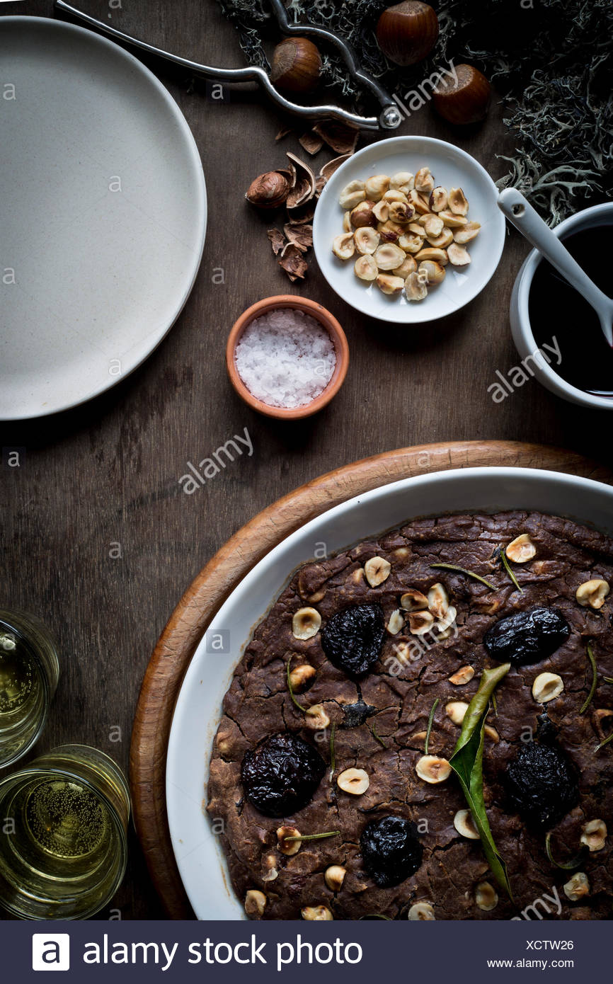 Festive Mediterranean Chestnut Flour Cake in white dish on set wooden table with ingredients, Christmas decoration, and wine gla - Stock Image