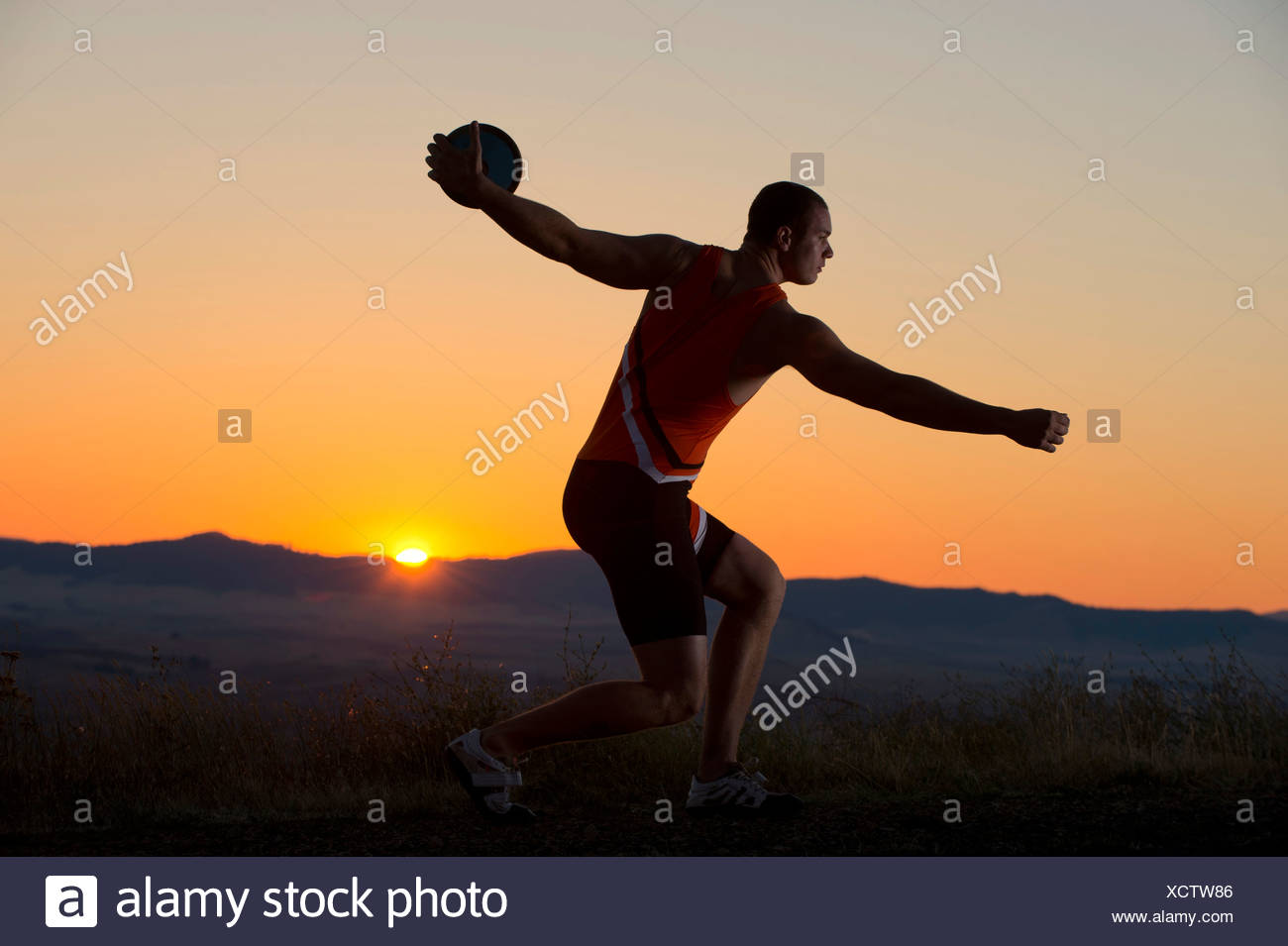 Young man preparing to throw discus at sunset - Stock Image
