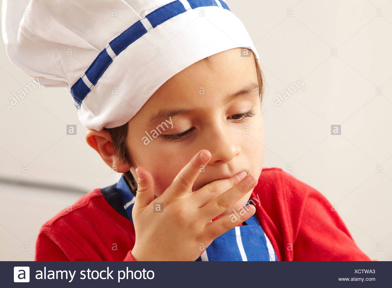 Close up of young boy licking fingers - Stock Image