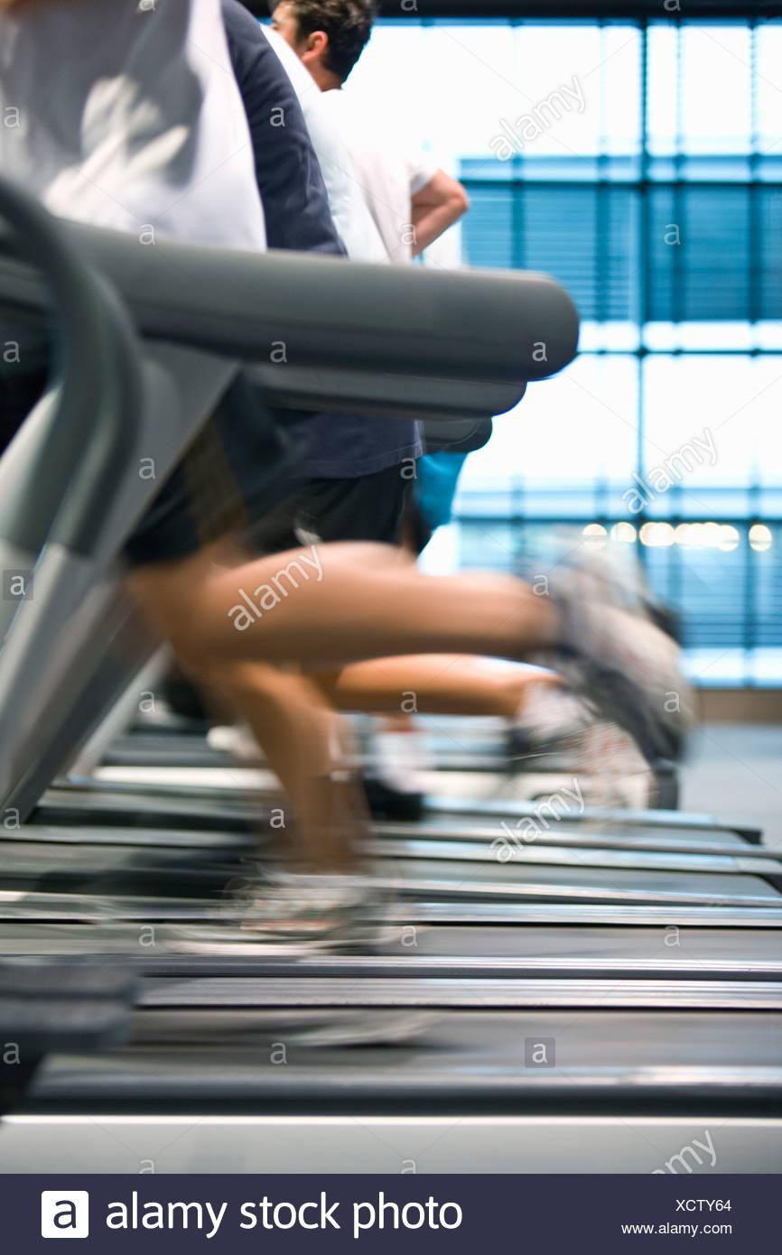 People running on treadmills in health club - Stock Image