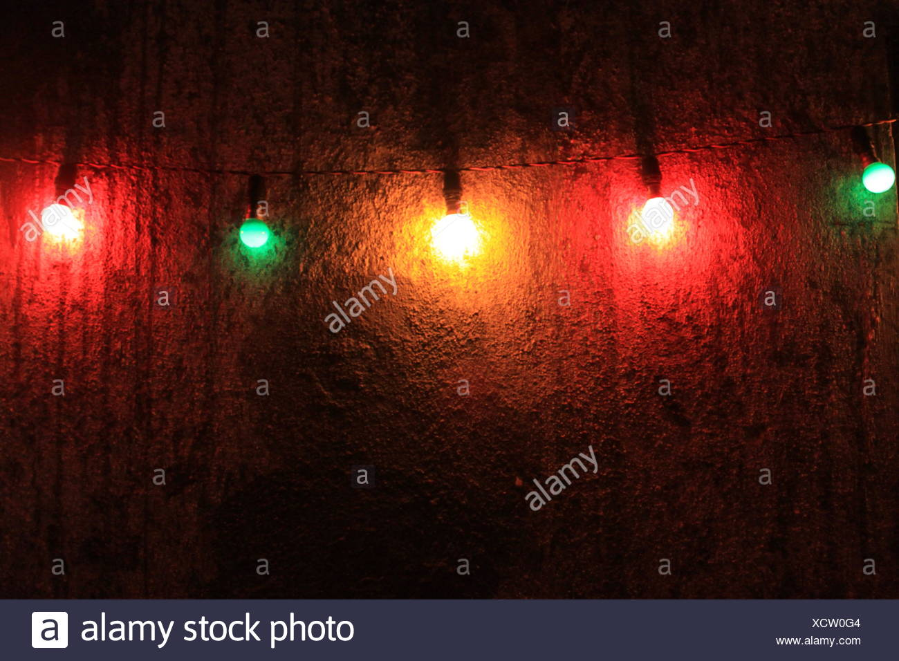 Multi-colored lights hanging on a wall Stock Photo