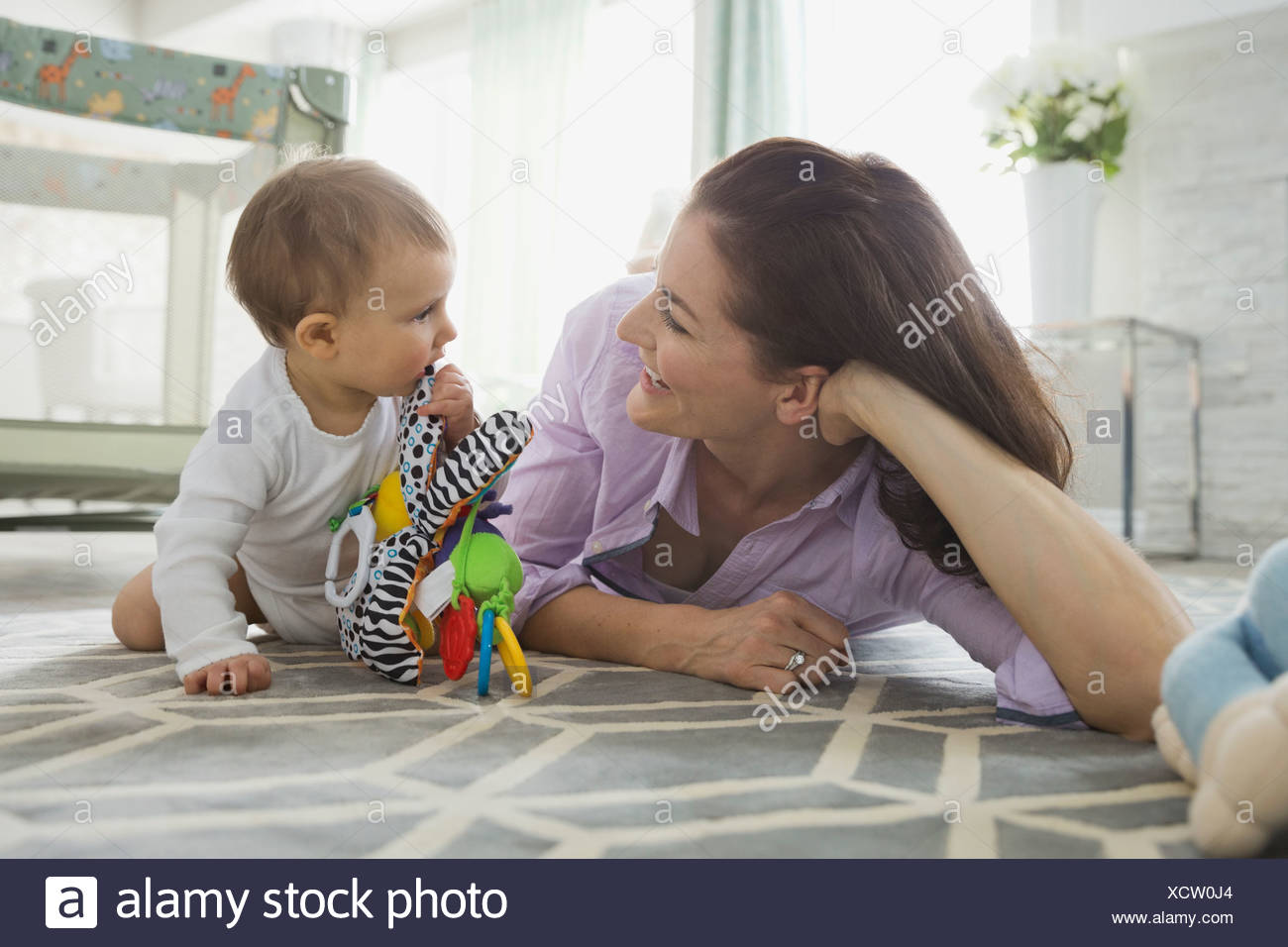 Cheerful mother playing with baby girl at home - Stock Image