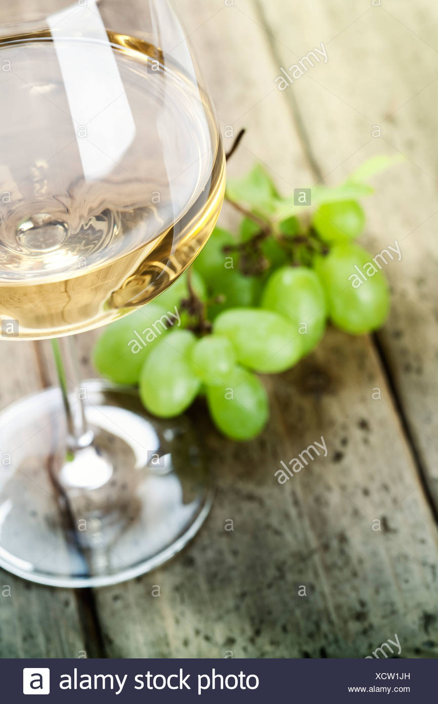 grape and wine on wooden table - Stock Image