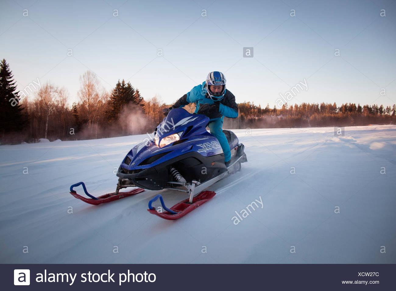 Sweden, Halsingland, Man driving snowmobile - Stock Image