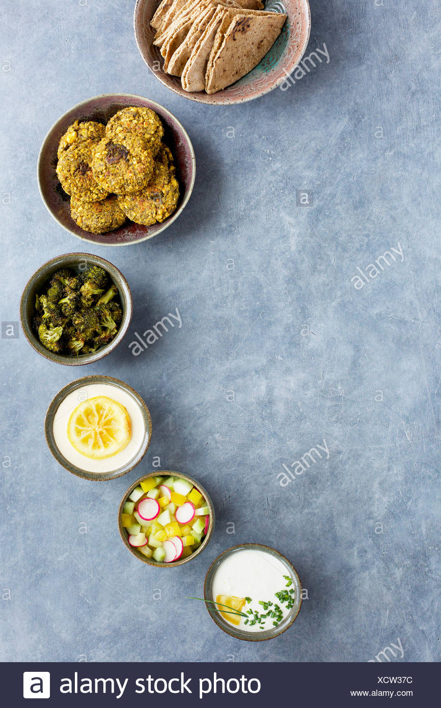 Ceramic bowls with charred broccoli falafel, charred lemon tahini, charred lemon tzatziki, charred broccoli, veggies and pita br - Stock Image