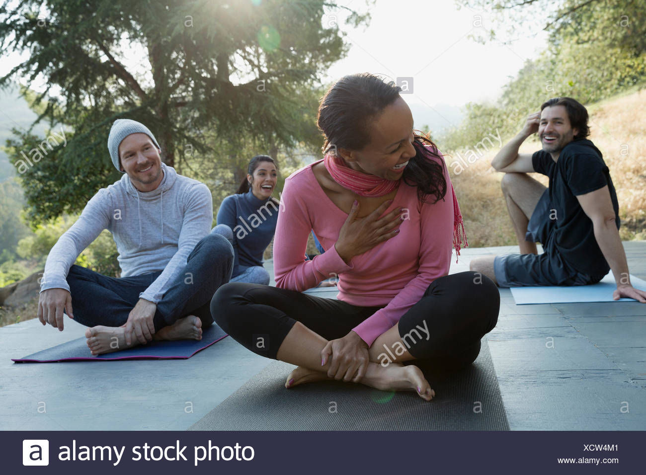 Laughing friends after yoga class on deck Stock Photo