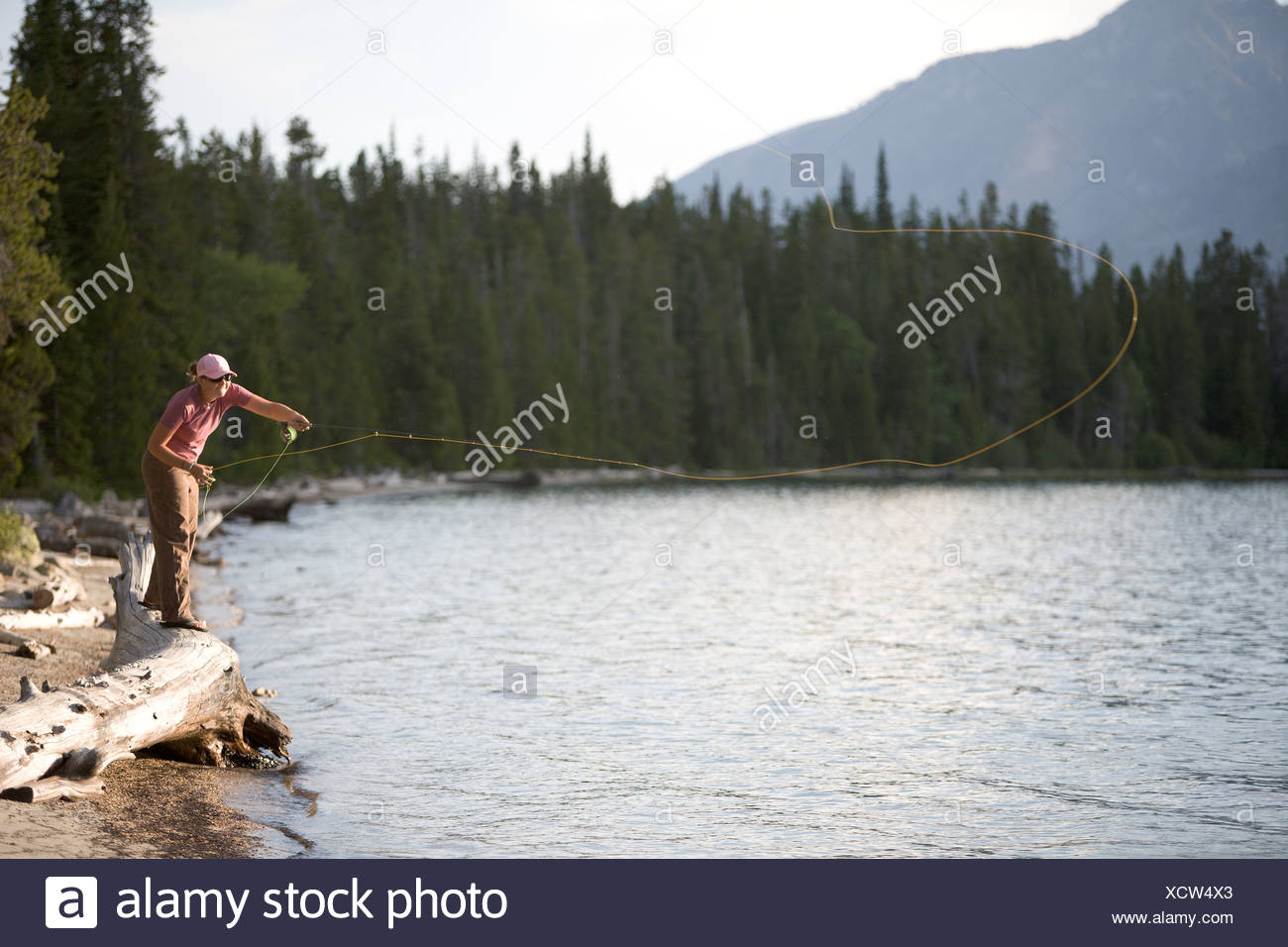 A woman casts her flyline from the shore of a lake. - Stock Image