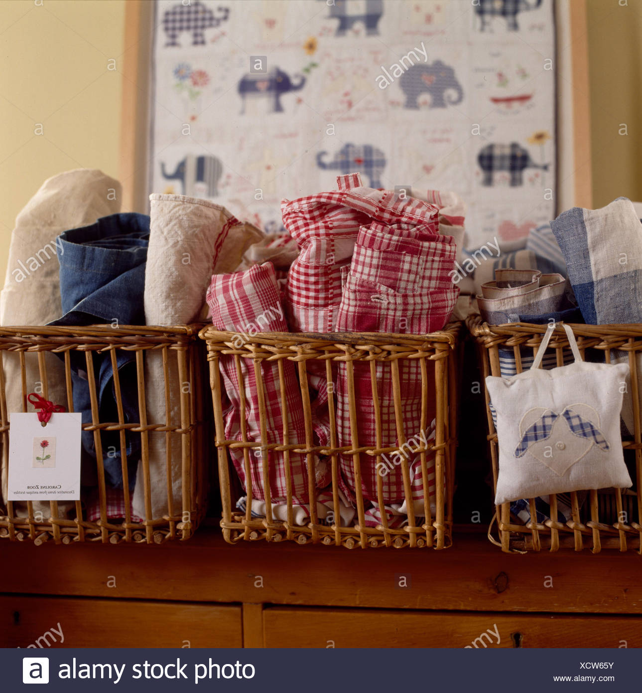 Baskets storing rolled towels and red checked tea towels - Stock Image