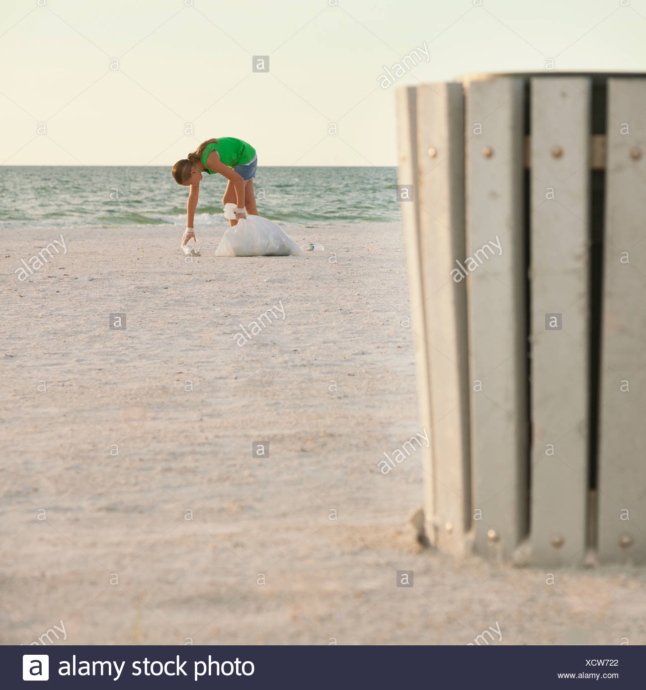 USA, Florida, St. Petersburg, Girl (10-11) cleaning beach, garbage bin in foreground - Stock Image
