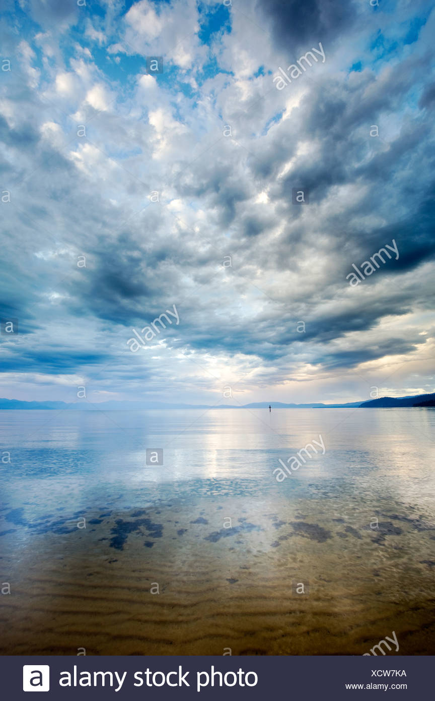 Clouds reflect off the calm waters of Lake Tahoe just after a storm, CA. - Stock Image