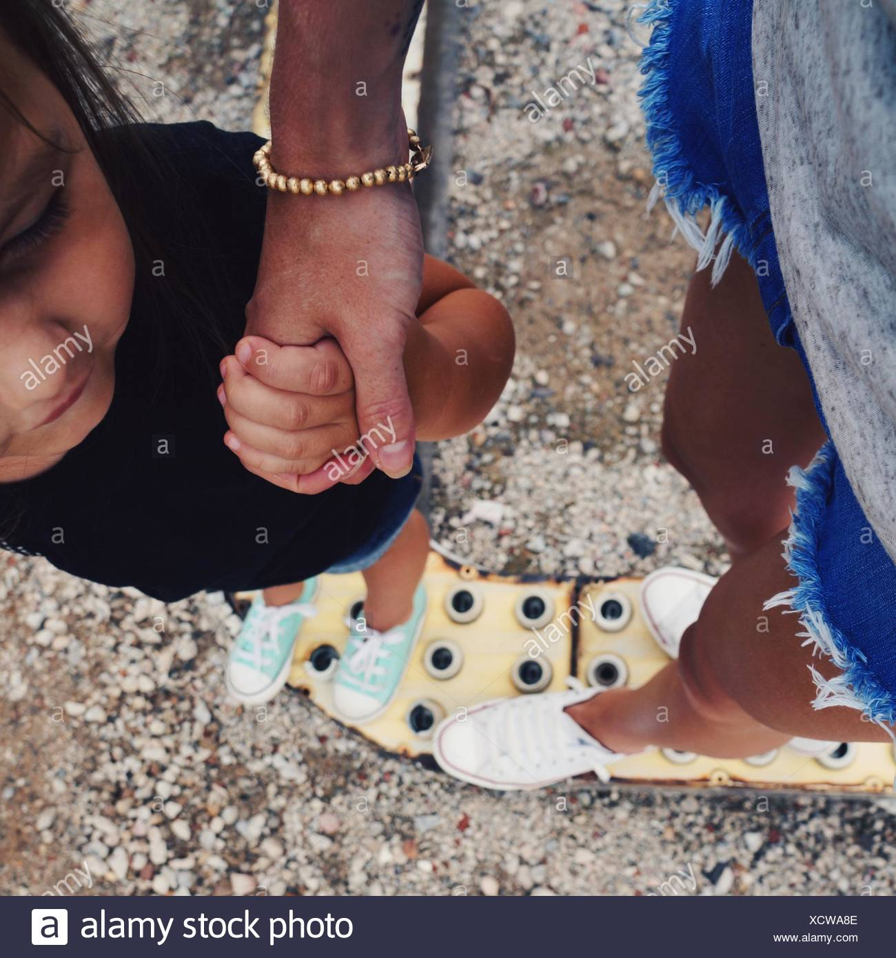 Cropped Mother Holding Hands With Daughter - Stock Image