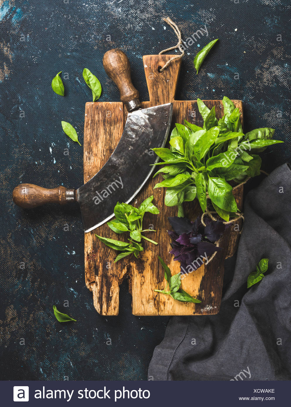 Fresh green and purple basil leaves with herb chopper knife on rustic cutting board over grunge dark blue plywood texture. Top v - Stock Image
