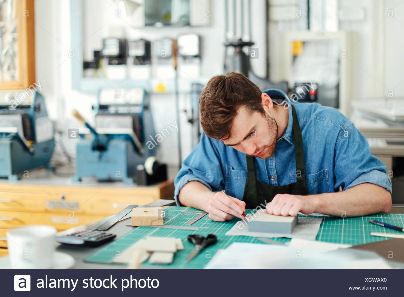 Young craftsman using scalpel and making work in print studio - Stock Image