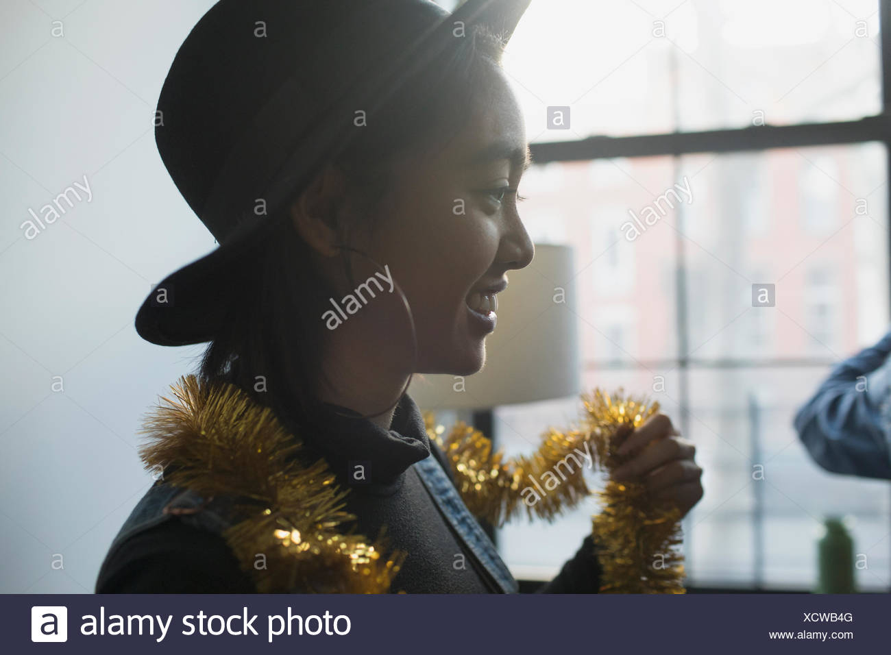 A young woman wearing tinsel - Stock Image