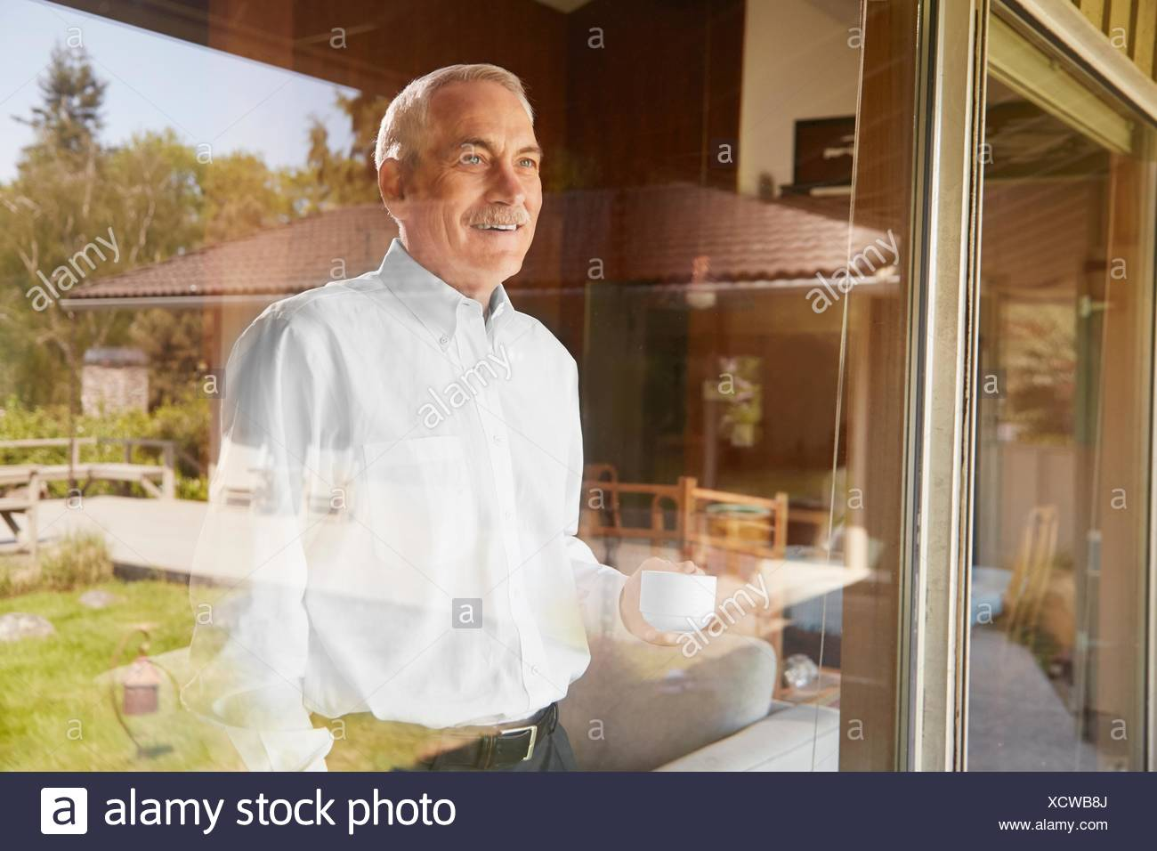 Senior man at home, drinking coffee, looking out of window - Stock Image