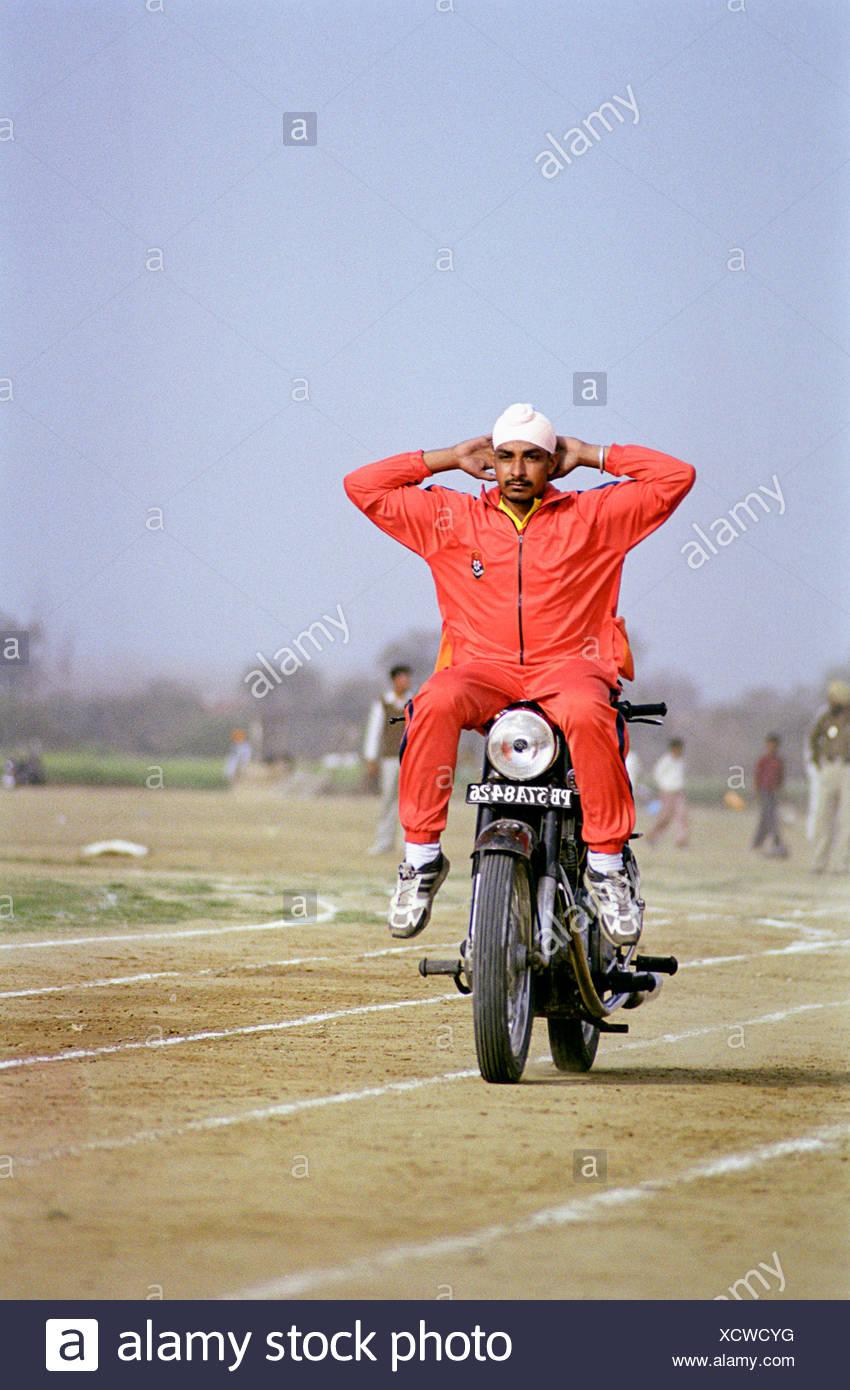 Stuntman performing at rural Olympic games Kila Raipur Punjab India - Stock Image