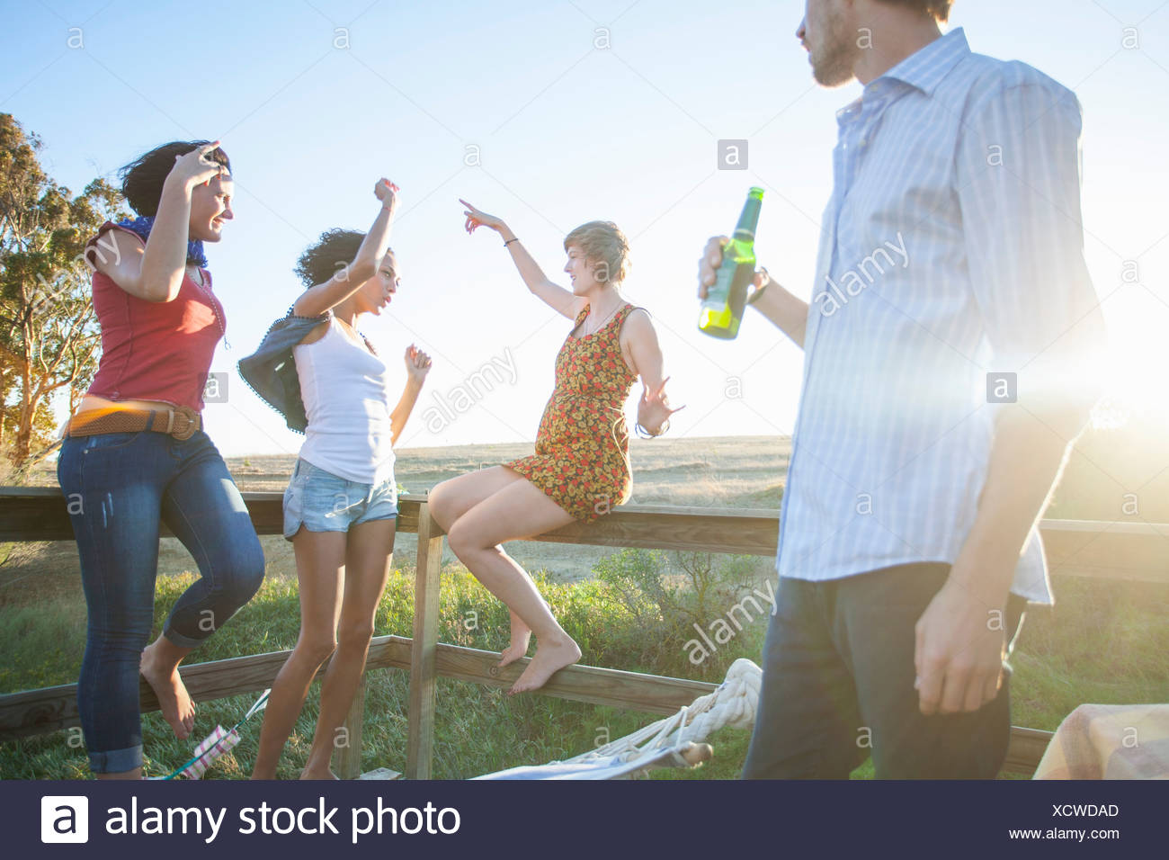 Young man watching friends dance on balcony - Stock Image