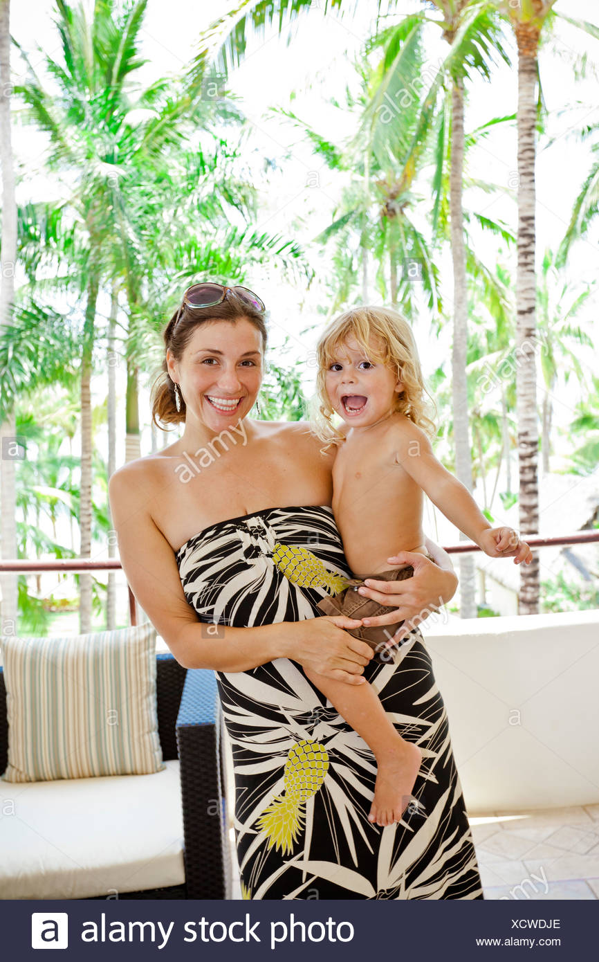 Stylish woman with baby near palm trees Stock Photo
