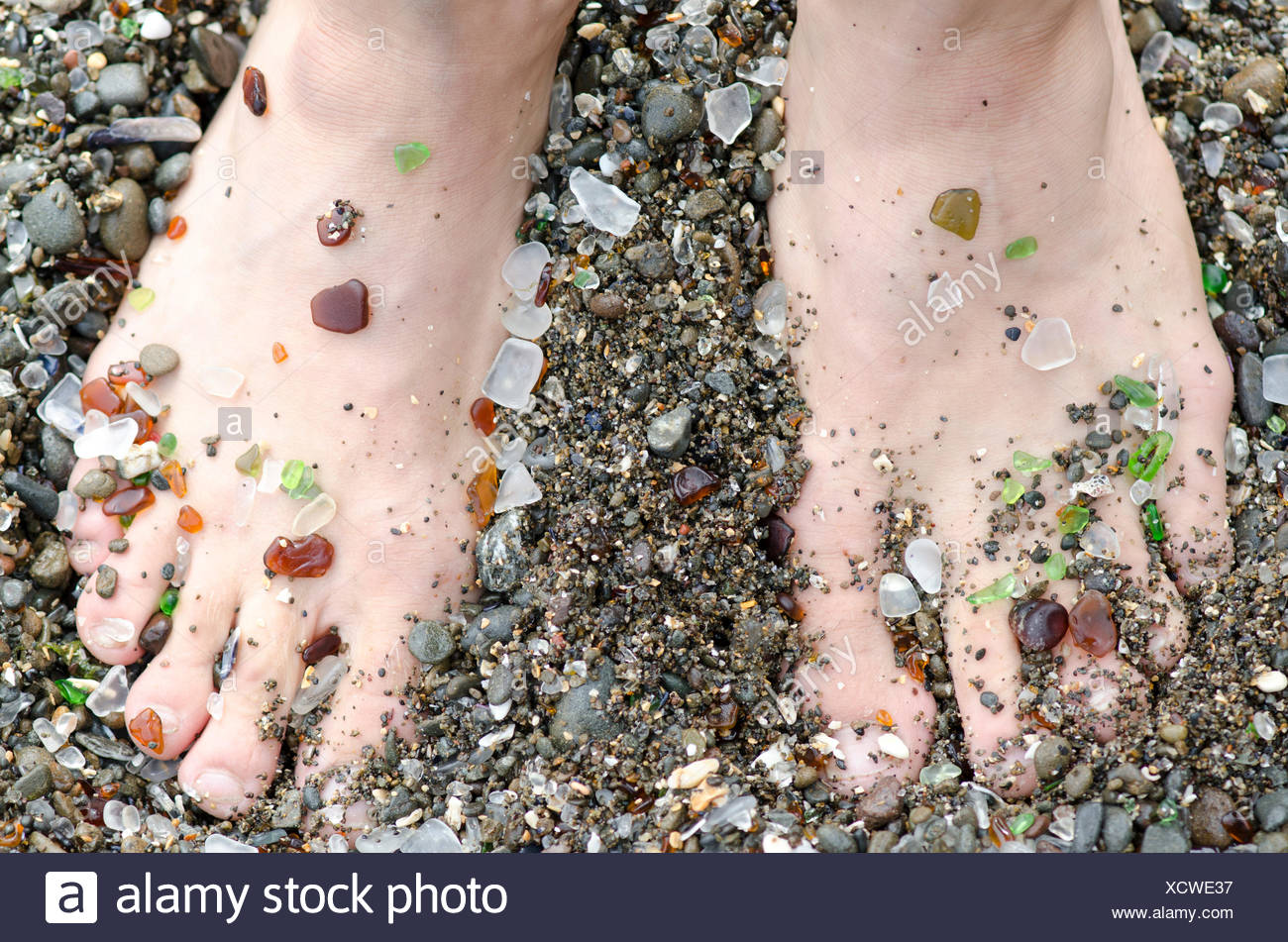 A mans feet are covered in glass from the handfuls of beach glass that wash ashore at Glass Beach in Fort Bragg, California. - Stock Image
