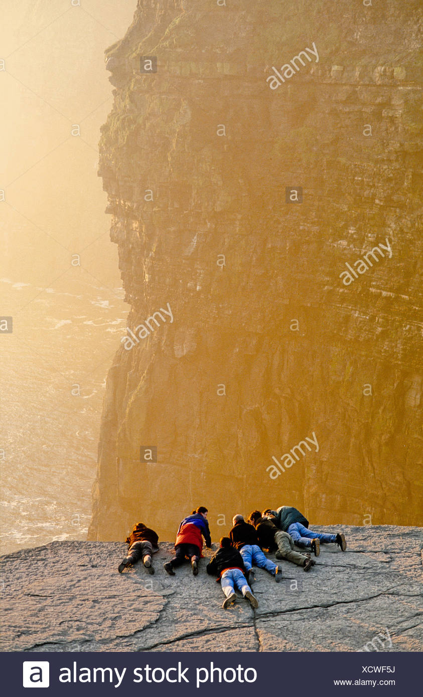 People on the cliff edge at Cliffs of Moher Ireland - Stock Image