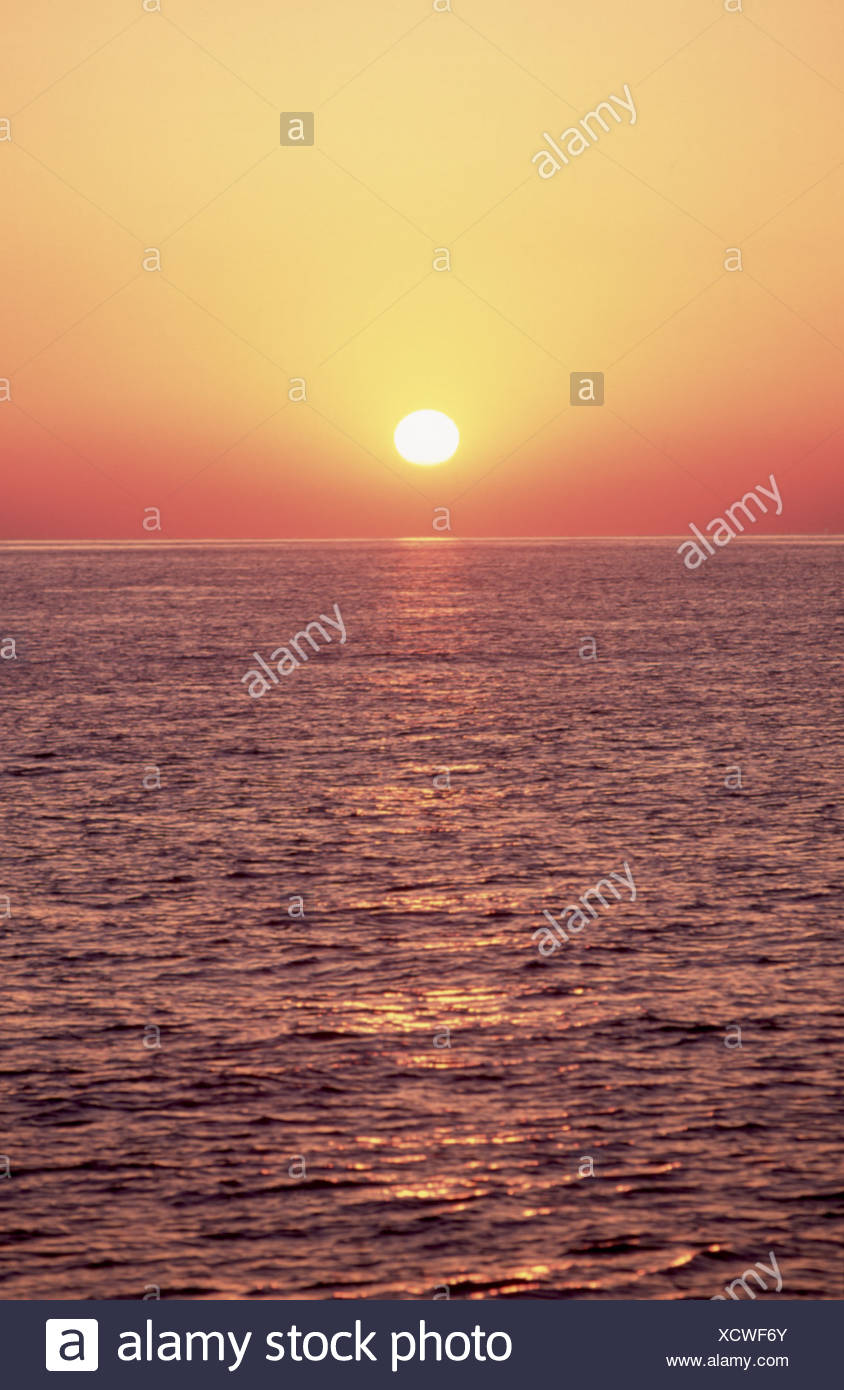 Sunset of the Mediterranean with the setting sun reflecting in gently rippling water - Stock Image