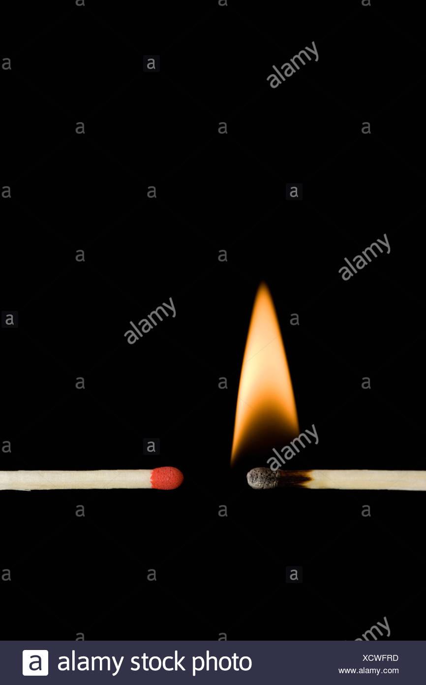 A lit matchstick next to an unlit matchstick - Stock Image