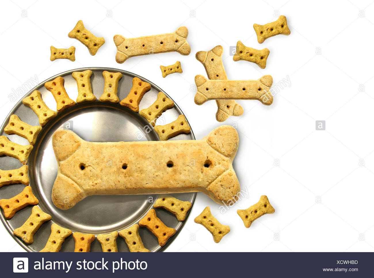 Pile of doggy biskets with pewter dish - Stock Image