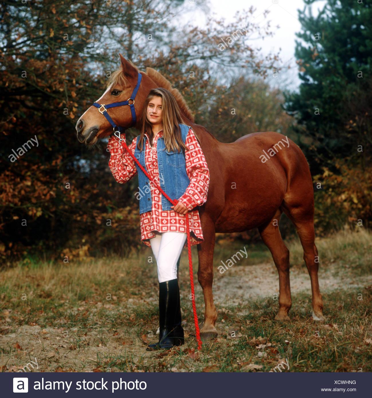 Teenage girl horse lover outside look at camera full length shot - Stock Image