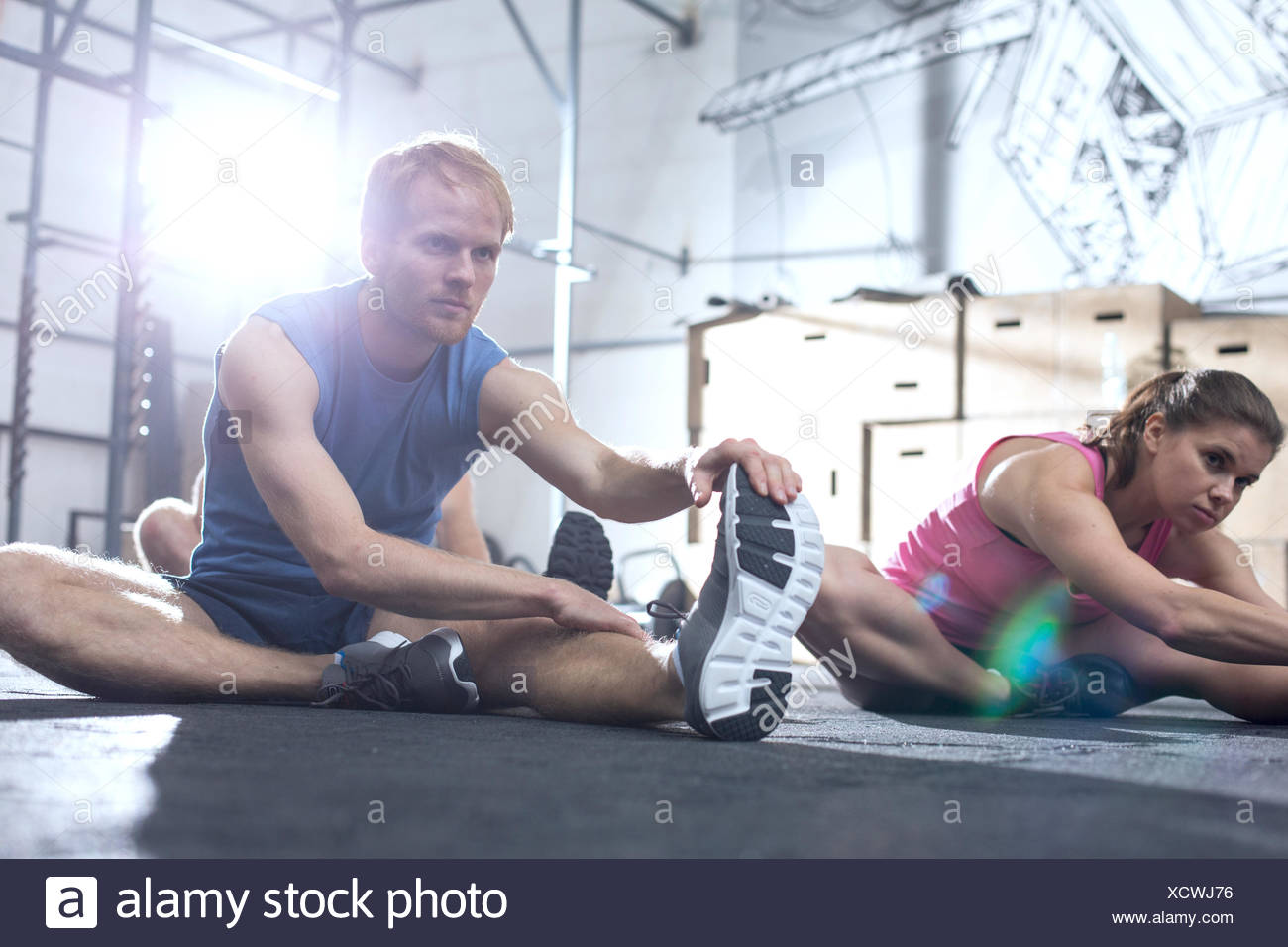 Confident man and woman doing stretching exercise in crossfit gym - Stock Image